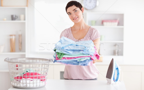 Beautiful Woman with a pile of clothes in a utility room Stock photo © wavebreak_media