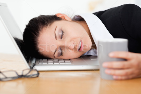 An exhausted businesswoman is sleeping with her head on her keyboard Stock photo © wavebreak_media