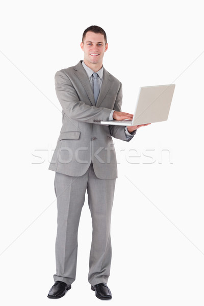 Portrait of a young businessman holding a laptop against a white background Stock photo © wavebreak_media