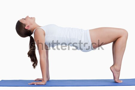 Stock photo: Woman practicing gymnastic against a white background