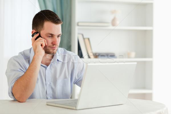 Young businessman in his homeoffice calling Stock photo © wavebreak_media