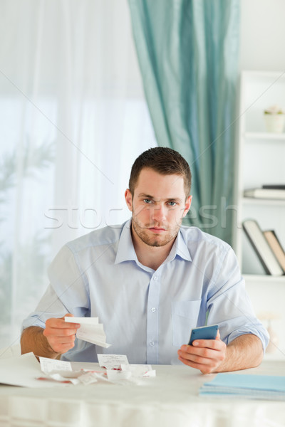 Serious looking young businessman doing accounting Stock photo © wavebreak_media