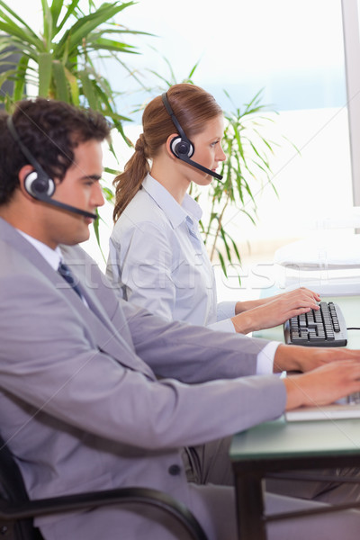 Stock photo: Young call center agents working next to each other