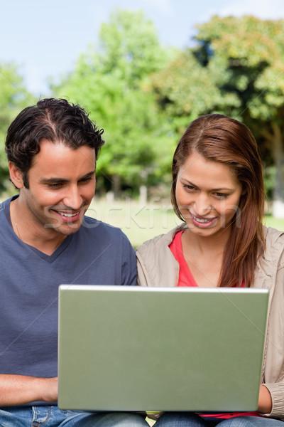 Dos amigos sonriendo felizmente ver algo Foto stock © wavebreak_media