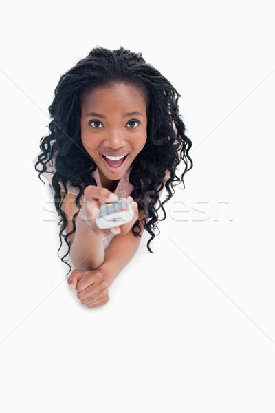 Giovani sorpreso donna punta televisione remote Foto d'archivio © wavebreak_media