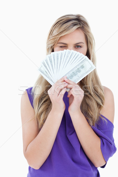 Young blonde woman blinking an eye while holding a fan of bank notes Stock photo © wavebreak_media