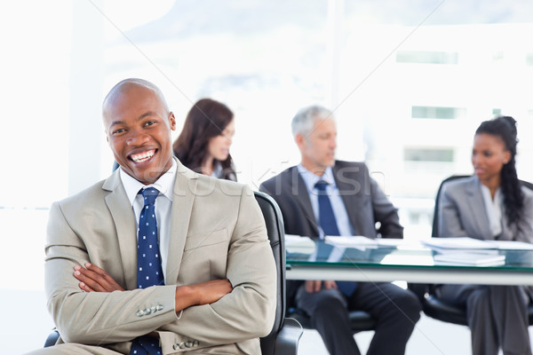 Young executive laughing while crossing his arms and sitting in front of his team Stock photo © wavebreak_media