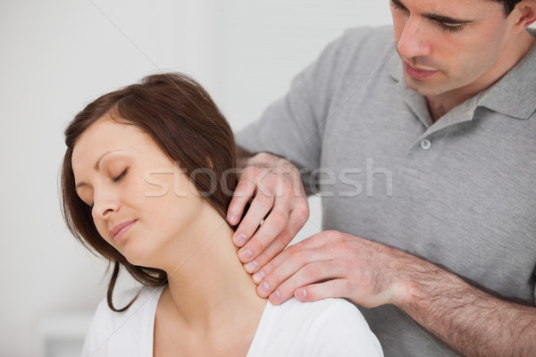 Man massaging the neck of his patient in a medical room Stock photo © wavebreak_media