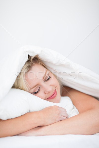 Young woman sleeping peacefully in her bed Stock photo © wavebreak_media