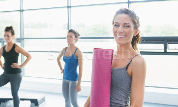 Woman holding a mat and two other women in gym Stock photo © wavebreak_media