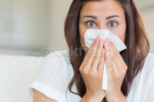 Brunette sneezing into tissue Stock photo © wavebreak_media
