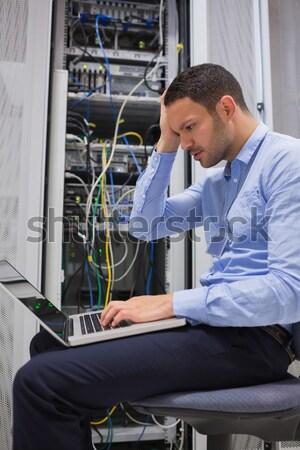 Smiling man using the laptop next to servers in data center Stock photo © wavebreak_media