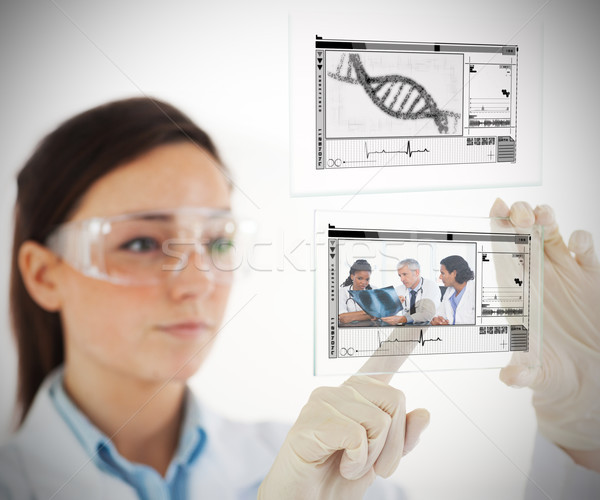 Lab technician selecting medical image from hologram interface on white Stock photo © wavebreak_media