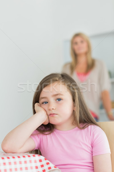 Little girl looking annoyed sitting at kitchen table with mother in background Stock photo © wavebreak_media