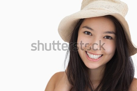 Smiling woman with a straw hat on white background Stock photo © wavebreak_media