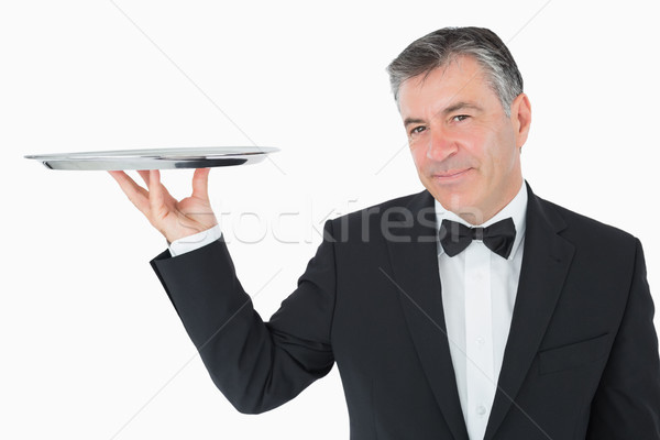 Well-dressed waiter holding a silver tray in front of camera Stock photo © wavebreak_media