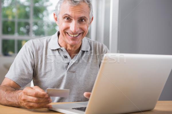 Smiling mature man using his laptop Stock photo © wavebreak_media