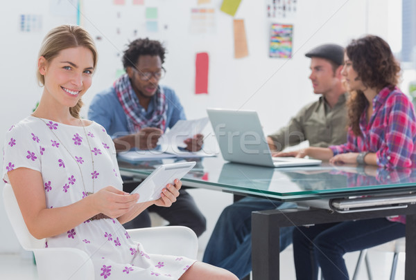 Stock photo: Editor holding tablet and smiling as team works behind her