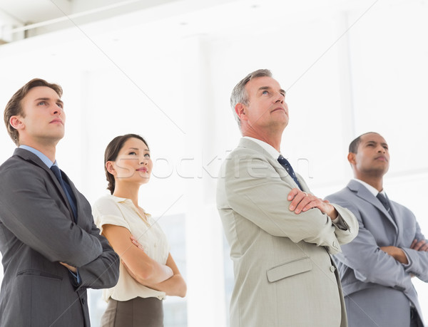 Serious business team with arms crossed looking up Stock photo © wavebreak_media