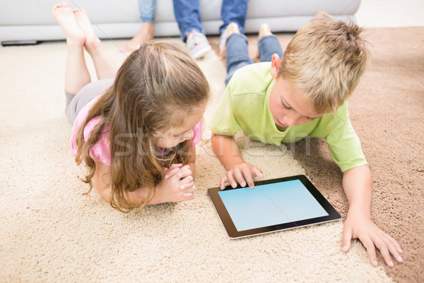 Smiling siblings lying on the rug using a tablet Stock photo © wavebreak_media