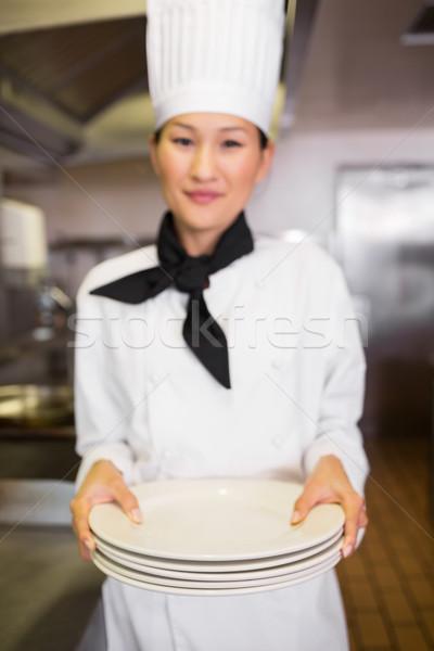 Lächelnd weiblichen Koch halten leer Platten Stock foto © wavebreak_media