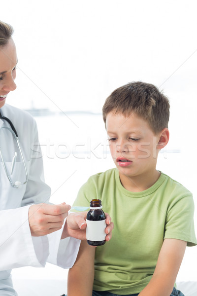 Doctor giving little boy syrup Stock photo © wavebreak_media
