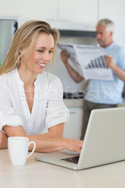 Glimlachende vrouw met behulp van laptop partner permanente papier home Stockfoto © wavebreak_media