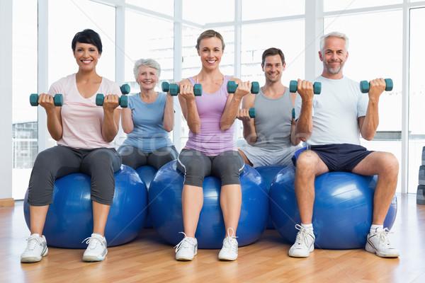 Fitness class with dumbbells sitting on exercise balls Stock photo © wavebreak_media