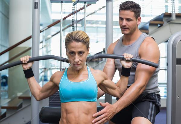 Female bodybuilder using weight machine for arms with encouragin Stock photo © wavebreak_media