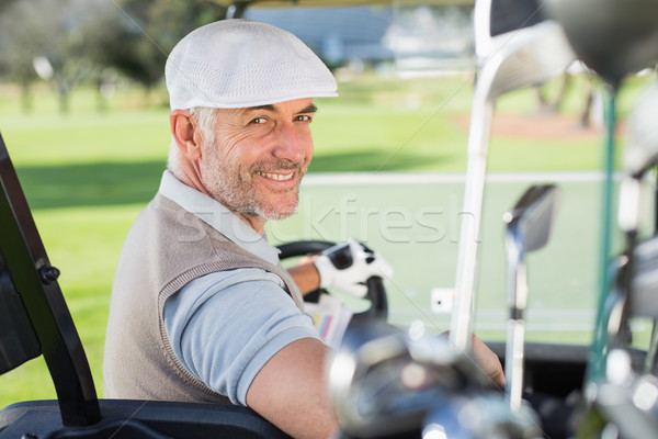 Happy golfer driving his golf buggy smiling at camera Stock photo © wavebreak_media