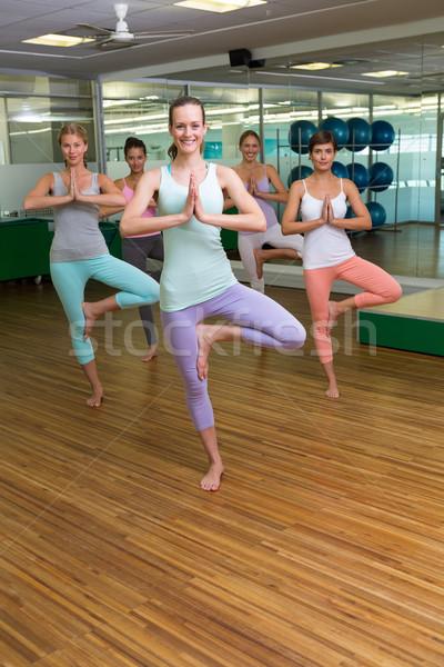 Smiling yoga class in tree pose in fitness studio Stock photo © wavebreak_media
