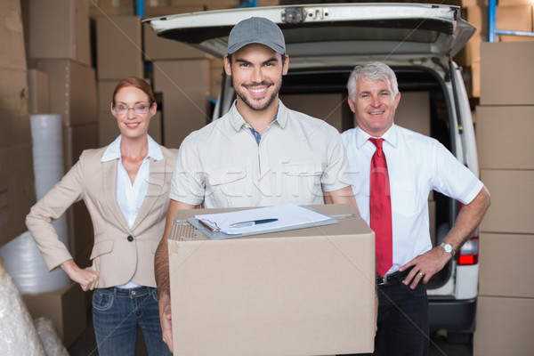 Warehouse managers and delivery driver smiling at camera Stock photo © wavebreak_media