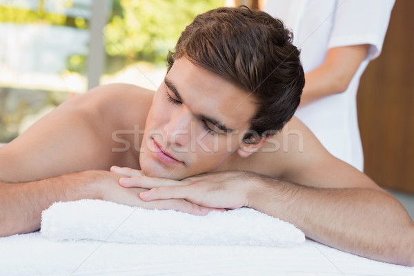Young man lying on massage table at spa center Stock photo © wavebreak_media