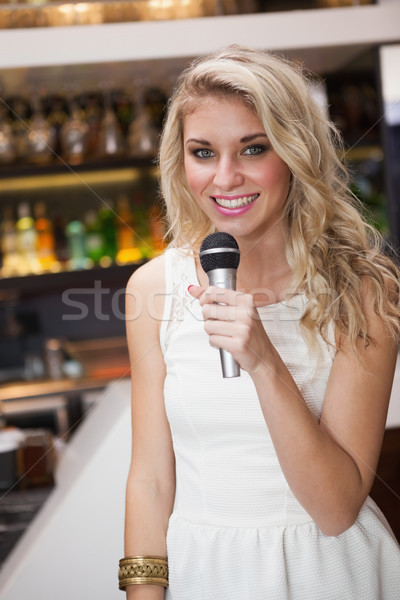 Blonde woman smiling while singing into a microphone Stock photo © wavebreak_media