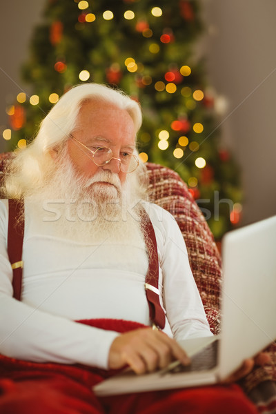 Father christmas typing on laptop Stock photo © wavebreak_media