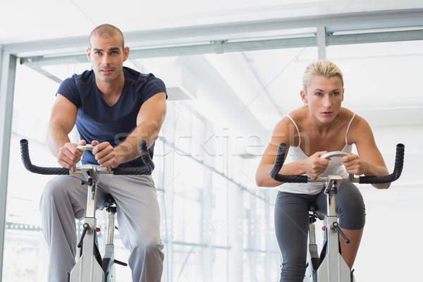 Determined fit couple working on exercise bikes at gym Stock photo © wavebreak_media