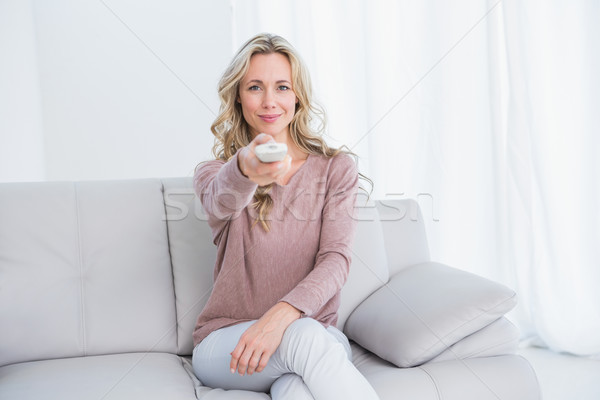 Smiling blonde on couch changing tv channel Stock photo © wavebreak_media