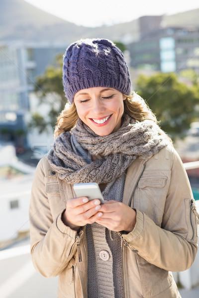 Mosolyog szőke nő meleg ruházat sms üzenetküldés város Stock fotó © wavebreak_media