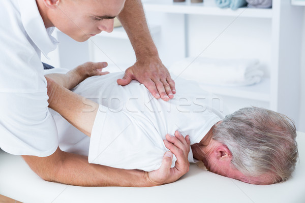 Physiotherapist doing shoulder massage to his patient Stock photo © wavebreak_media