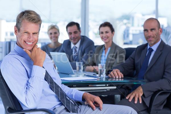 Zakenman glimlachend camera collega's achter kantoor Stockfoto © wavebreak_media