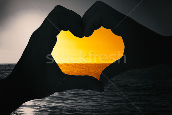 Composite image of couple making heart shape with hands Stock photo © wavebreak_media