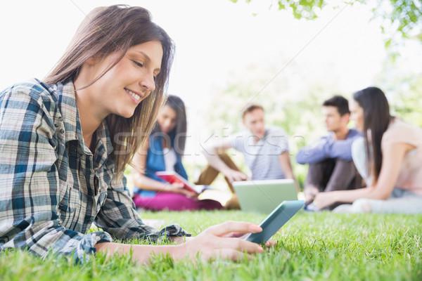 Szczęśliwy studentów posiedzenia na zewnątrz kampus uczelni Zdjęcia stock © wavebreak_media