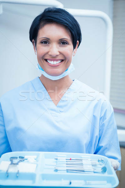 Female dentist in blue scrubs holding tray of tools Stock photo © wavebreak_media
