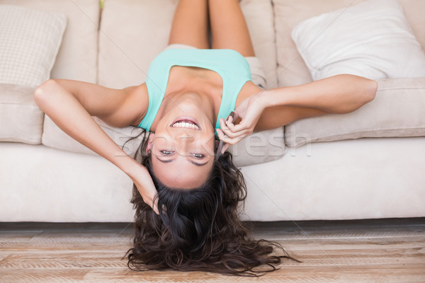 Pretty brunette lying upside down on couch  Stock photo © wavebreak_media