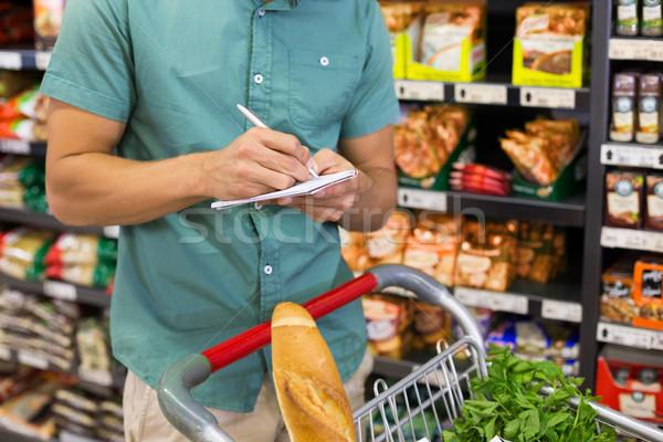 Hombre escrito bloc de notas supermercado mercado Foto stock © wavebreak_media