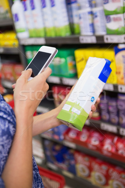 Woman comparing the price of a carton of milk with her phone Stock photo © wavebreak_media