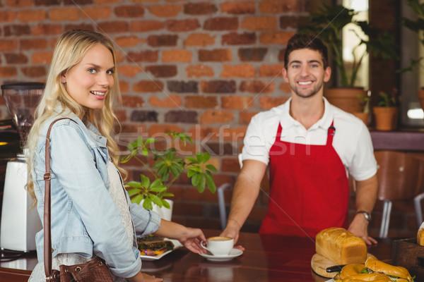Smiling barista serving a client Stock photo © wavebreak_media