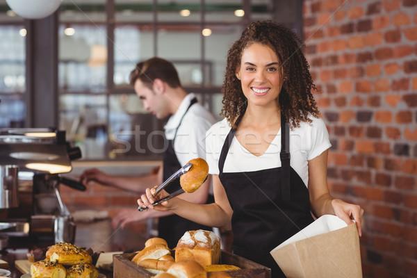 Uśmiechnięty kelnerka chleba toczyć torby papierowe portret Zdjęcia stock © wavebreak_media
