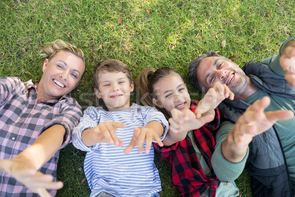 Stock photo: Happy family lying on the grass and making hand gestures
