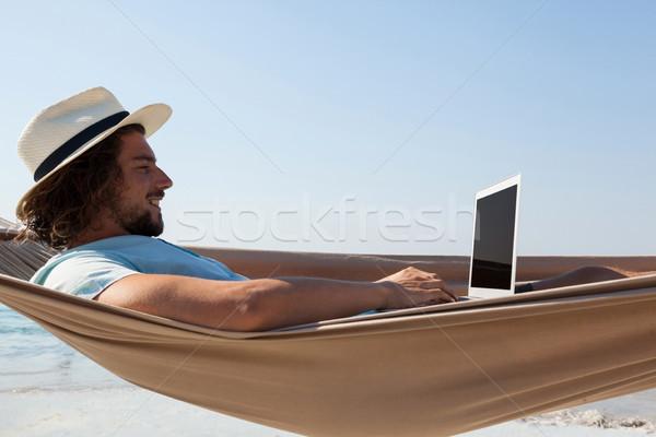 человека используя ноутбук расслабляющая гамак улыбаясь пляж Сток-фото © wavebreak_media